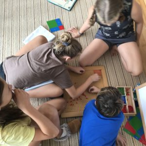 students work on Montessori math materials